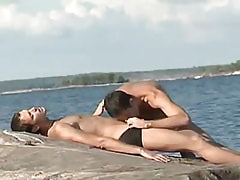 Sexy gay greedily throats cock on island